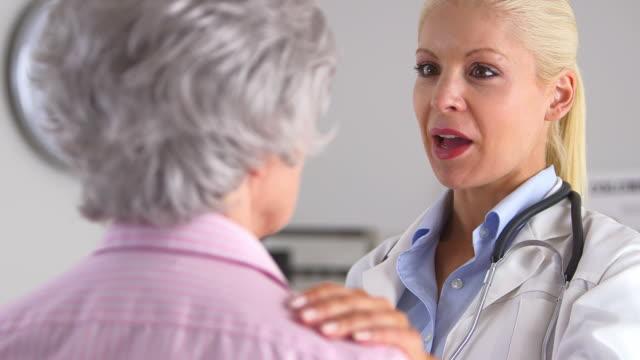 Doctor with hand on elderly patient's shoulder