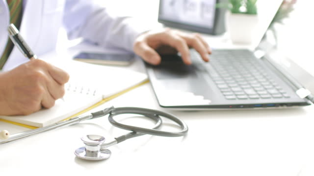Doctor working with laptop and take a note and filling out medical document , UHD format , Dolly shot panning right to left movement