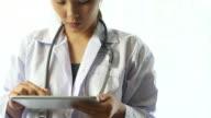 Doctor's hands using digital tablet on white Background