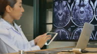 Doctors looking MRI scans on Digital Tablet PC