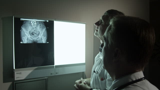 Doctors referencing a patient's pelvic x-ray.