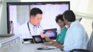MS Doctors Reviewing Brain Scans on Tablet Computer, Discussing with Colleague via Video Conference / Virginia Beach, Virginia, USA