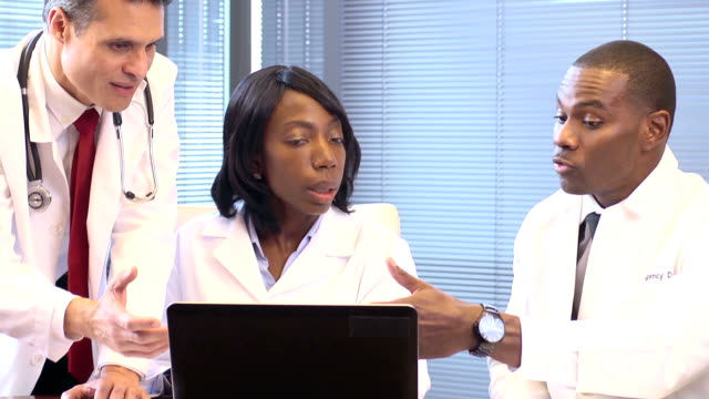 Doctors Use Laptop Computer and Discussing Case