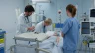 DS artsen bezoekende jonge vrouwelijke patiënt op hun ronde in de ICU
