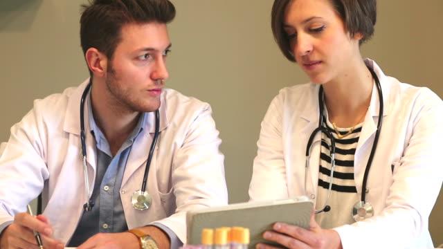 Ärzte arbeiten mit Tablette und Schreiben ein Rezept