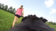 POV Dog and female owner running and playing in meadow