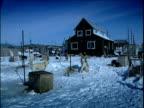 Dogs loiter outside houses in Eskimo village Alaska