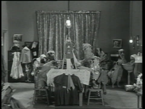 B/W 1930 dogs sitting in chairs at table / one leaning by sink / Dogway Melody