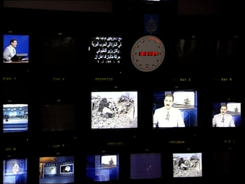 Doha GV Presenter sitting at desk in Al Jazeera TV news studio as preparing for broadcast CS Autocue scrolling up BV Producers working in control...