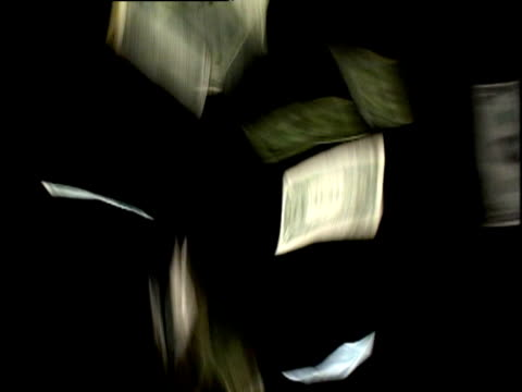 Dollar bills fall through air against black background