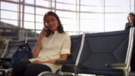 Dolly around woman talking on cell phone while waiting for flight at airport to woman sitting down behind her and removing laptop from bag / working on laptop