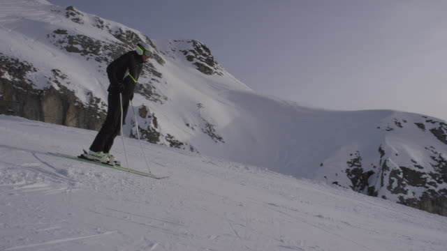Dolly of lone skier skiing down slope.
