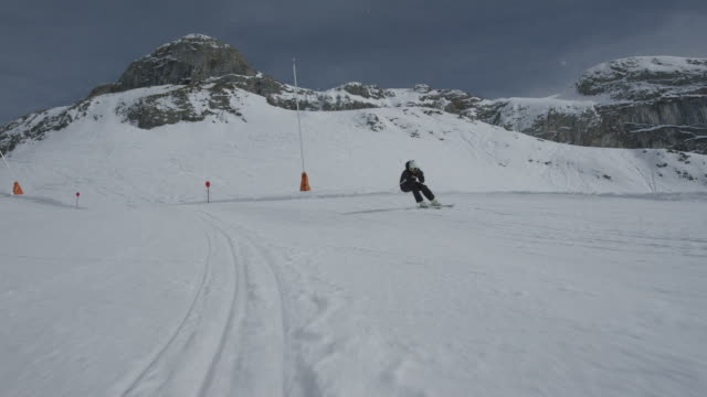 Dolly of lone skier skiing slalom downhill with the camera in front.