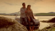 Dolly past couple leaning against hood of convertible car parked on rocky shore