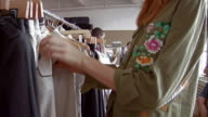Dolly past team of young fashion designers and stylists looking through racks of clothes
