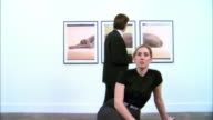 Dolly past woman sitting on bench at gallery opening and looking at artwork across room / man looking at three-panel print of a Weimaraner by William Wegman on wall behind woman