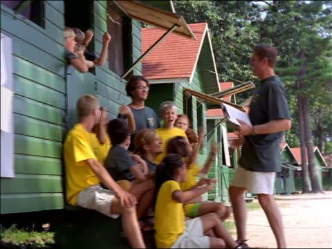 dolly shot around male camp counselor cheering on group of children outside green cabin