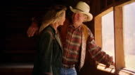 MS dolly shot away from man in cowboy hat looking out window / woman goes to him / they hug + smile