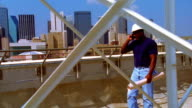 SHAKY dolly shot Black male construction worker walks + talks on cellular phone on roof/Dallas skyline in background