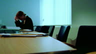 BLUE dolly shot businesswoman looking stressed sitting alone at table in conference room after meeting