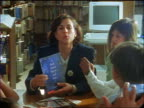 dolly shot female teacher talking to + showing book to kindergarten children sitting in school library