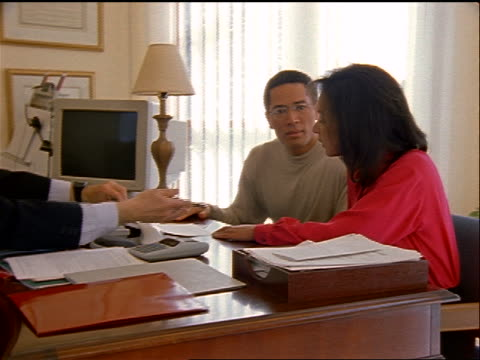 dolly shot financial advisor/banker using calculator, writing on paper + giving it to Black couple to sign
