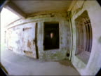 dolly shot FISHEYE PORTRAIT away from man standing in window quickly down long portico