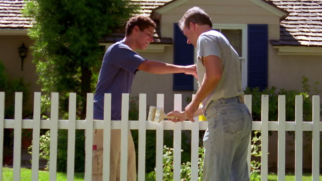 MS dolly shot grey haired man + teenage boy painting white fence with house in background