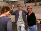dolly shot group of teens hanging out by chain link fence talking