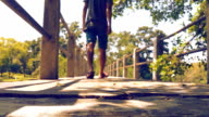 Dolly shot HD: Man walking on bridge in the park