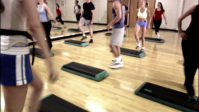 Dolly shot instructor and students in step aerobics class