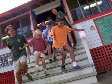 CANTED dolly shot large group of children + camp counselors running through doors of building + down stairs