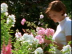 dolly shot low angle young woman picking flowers from flower garden