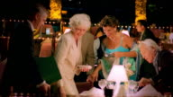 MS dolly shot PAN maitre d' seating two mature couples at table in upscale restaurant and giving them menus