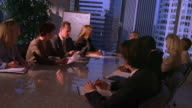 Dolly shot male executive speaking to businesspeople in meeting, using pie chart