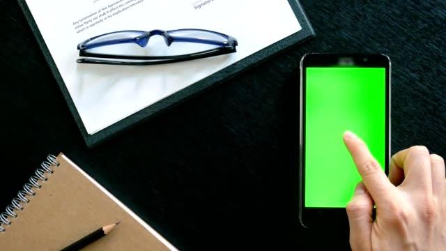 Dolly erschossen: Hand des Mannes über Mobiltelefon mit Greenscreen am Bürotisch - Draufsicht