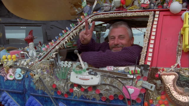 Dolly shot man in decorated art car gives peace sign / San Franisco Bay in background