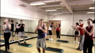 Dolly shot men and women clapping enthusiastically at the end of step aerobics class