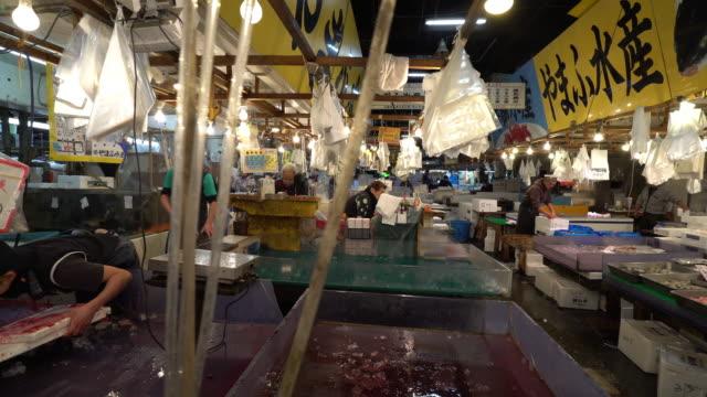 Dolly shot Merchant working at Tsukiji Fish Market Tokyo Japan