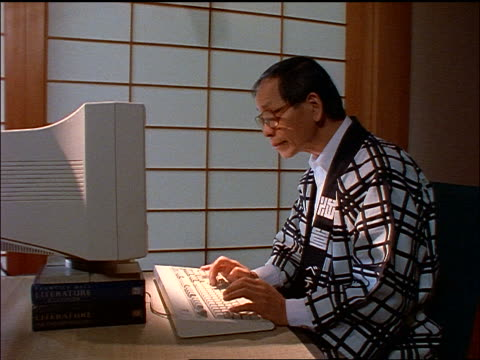 dolly shot middle aged Asian man in robe typing on computer
