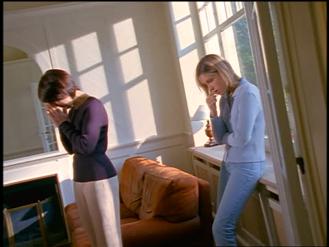 dolly shot mother having serious talk in living room with blonde teen daughter / they hug
