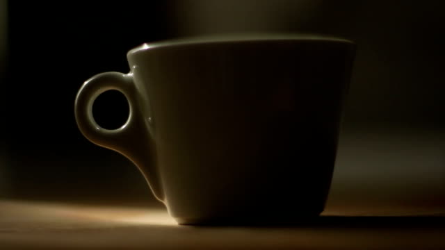 Dolly shot van een koffiekopje in donkere scene