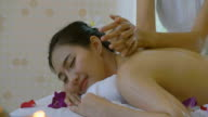 Dolly Shot of Beautiful Asian woman Enjoying Massage therapy with essential oils