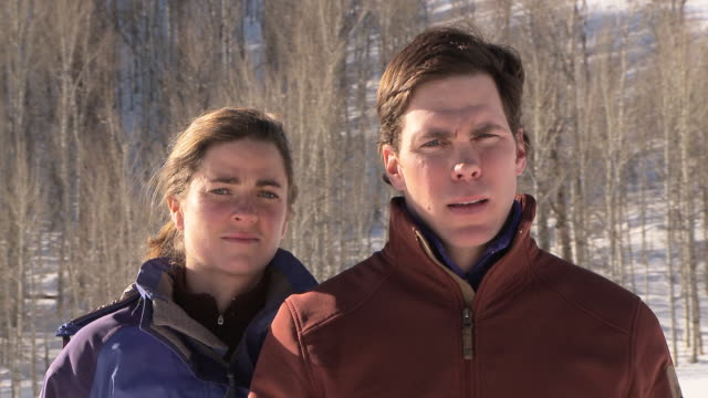 Dolly shot of couple outdoors in snow making eye contact with camera / Ketchum, Idaho, United States