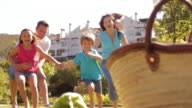 Dolly shot of family in park running towards picnic basket and twirling round.