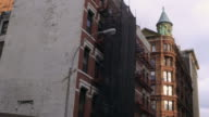 Dolly shot of old, big buildings in New York City.