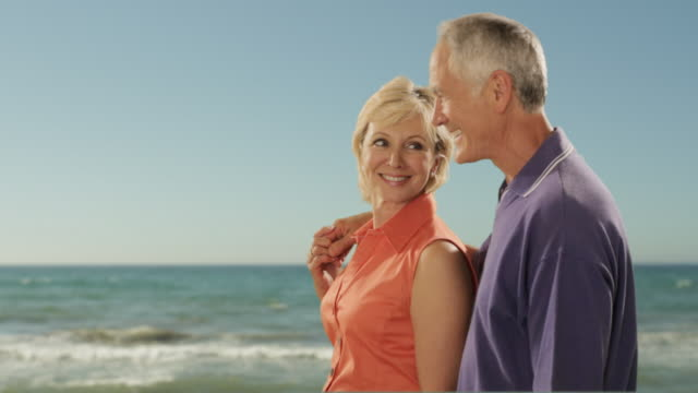 dolly shot of senior couple walking on beach with sea background