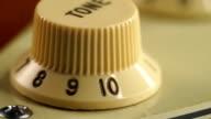 Dolly shot of Volume knob on guitar
