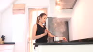 Dolly shot of woman cooking in modern kitchen