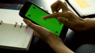 Dolly shot of woman hand using smart phone with blank Green Screen
